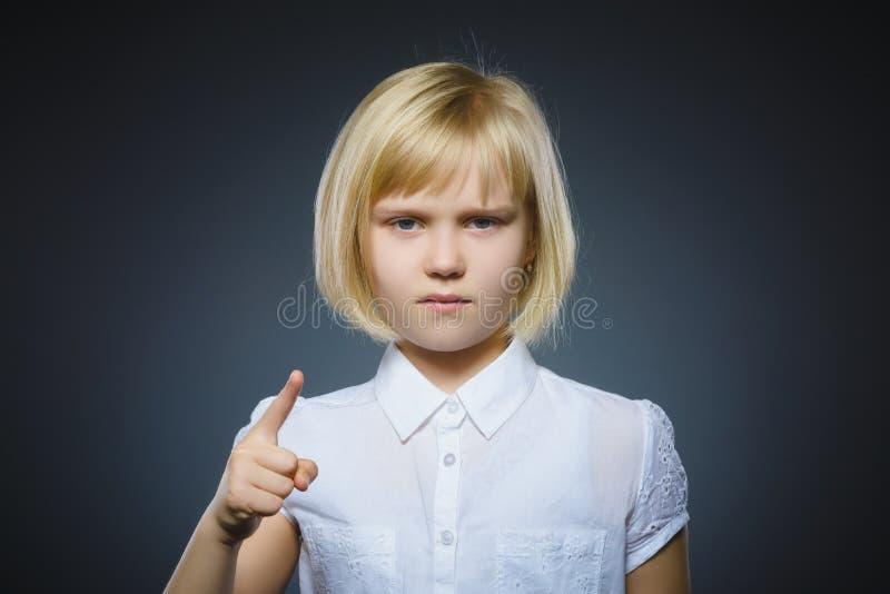 A menina irritada desagradada com ameaça o dedo isolado no fundo cinzento imagens de stock royalty free