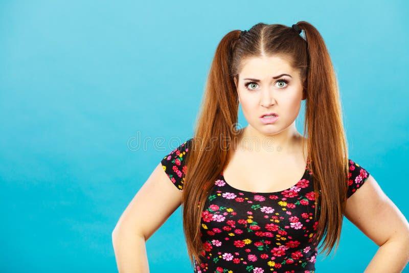 Menina irritada do adolescente com os rabos de cavalo marrons do cabelo fotografia de stock royalty free