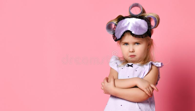 Menina irritada nos pijamas e em uma m?scara do sono, dobrou seus bra?os em uma pose em sua caixa e olhou de sobrancelhas franzid imagem de stock