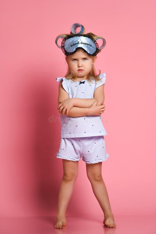 Menina irritada nos pijamas e em uma m?scara do sono, dobrou seus bra?os em uma pose em sua caixa e olhou de sobrancelhas franzid fotos de stock