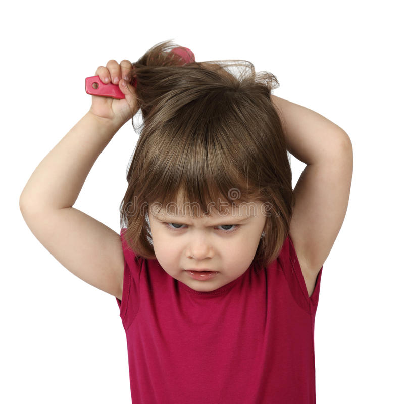 A menina irritada penteia seu cabelo imagens de stock