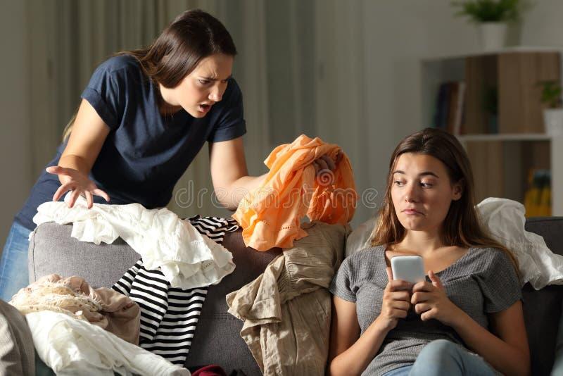 Menina irritada que discute seu companheiro de quarto desarrumado fotos de stock royalty free