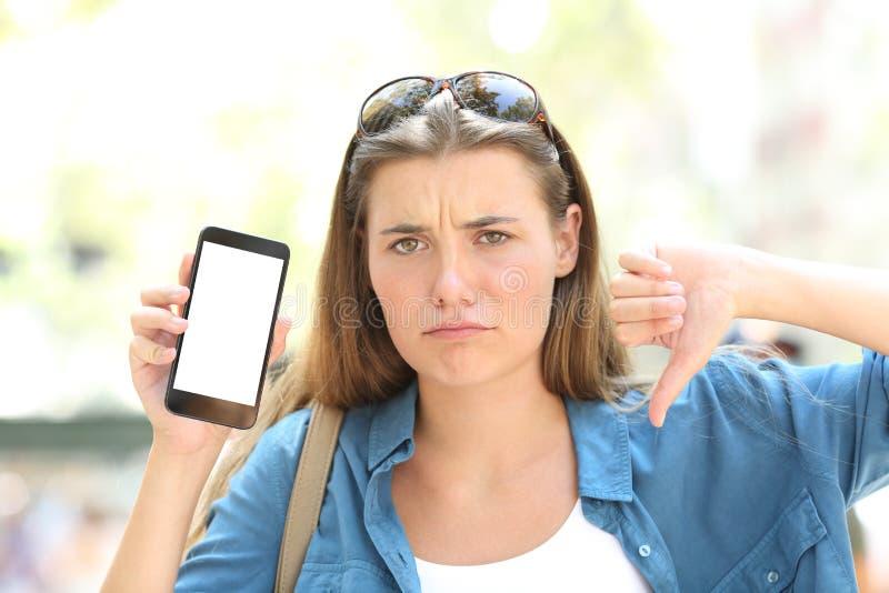 Menina irritada que mostra a tela vazia do telefone com polegar para baixo fotografia de stock