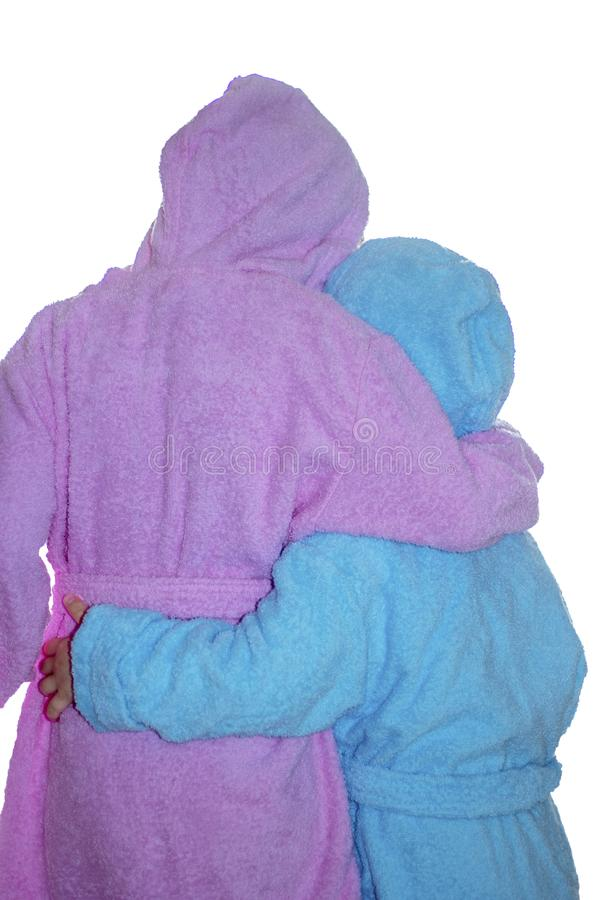 a menina isolada e o menino em roupões cor-de-rosa e azuis estão com suas partes traseiras que abraçam-se fotografia de stock royalty free