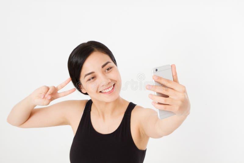A menina japonesa asiática do estudante novo faz o selfie em seu telefone celular isolado no fundo branco estudo ou fotografia de stock