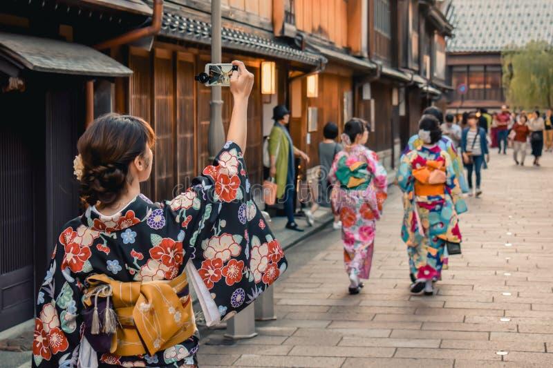 Menina japonesa no quimono que toma uma foto de uma rua tradicional com as casas de madeira em seu telefone em Kanazawa Japão fotografia de stock