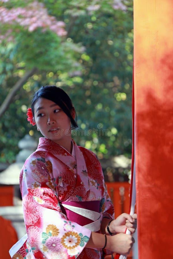 A menina japonesa no suporte do vestido do quimono e a tela da captura rope a soar o sino para abençoam no santuário em Japão imagens de stock