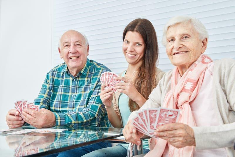 A menina joga cartões com pares dos sêniores imagem de stock royalty free