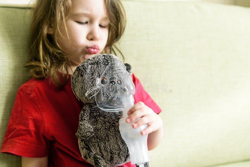 A menina joga com máscara do inalador em casa fotografia de stock
