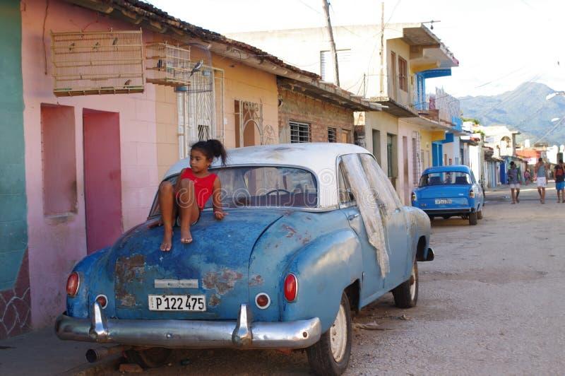 A menina joga em um carro velho estacionado em ruas das caraíbas fotografia de stock