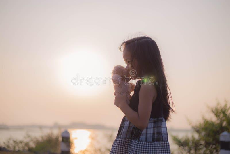 A menina joga felizmente sua boneca favorita no por do sol imagem de stock royalty free
