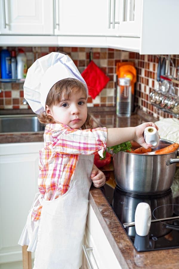 A menina joga o cozinheiro fotografia de stock royalty free
