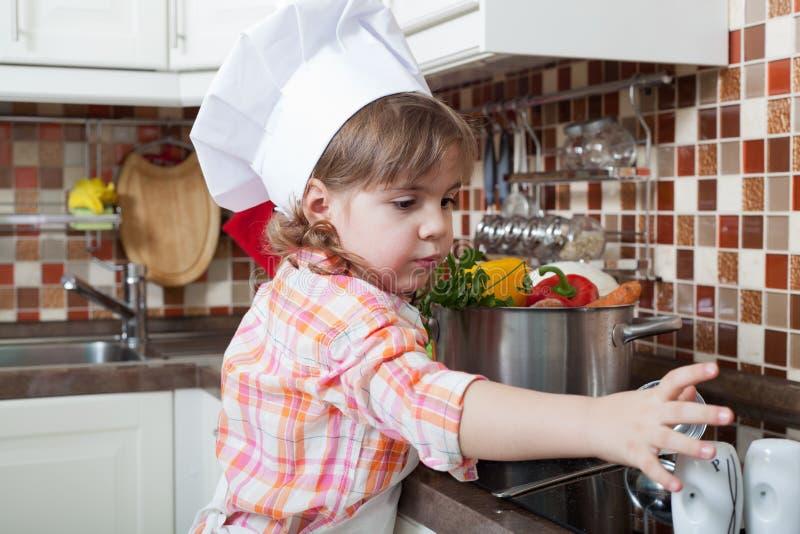 A menina joga o cozinheiro fotografia de stock