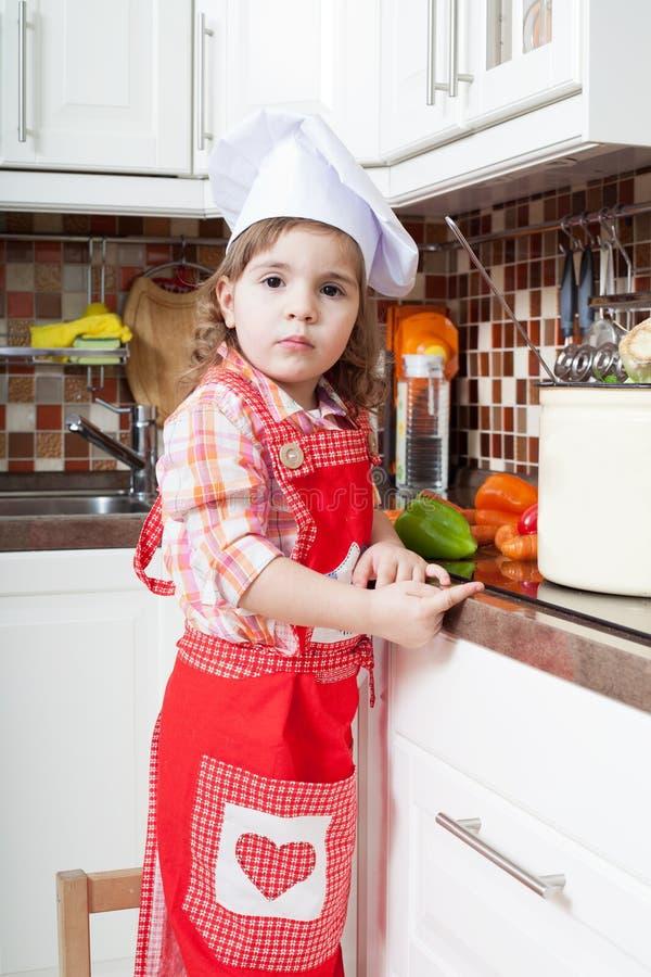 A menina joga o cozinheiro imagem de stock royalty free