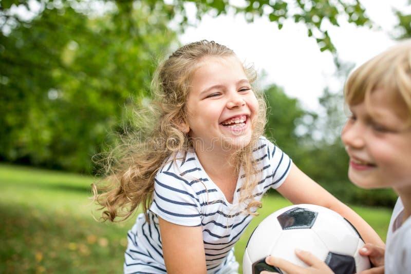 A menina joga o futebol com irmão fotografia de stock royalty free