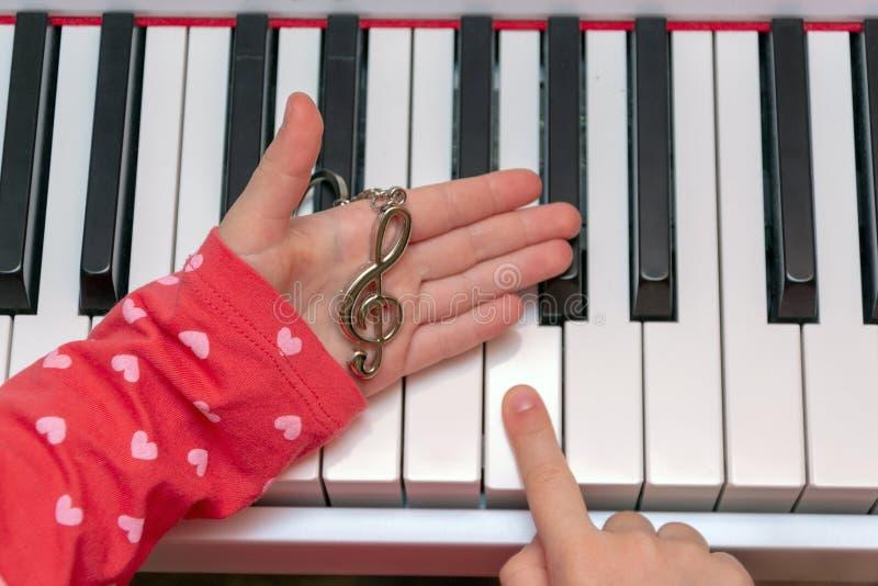 A menina joga o piano Mãos do músico nas chaves do piano ao jogar o instrumento Concerto da música clássica fotografia de stock