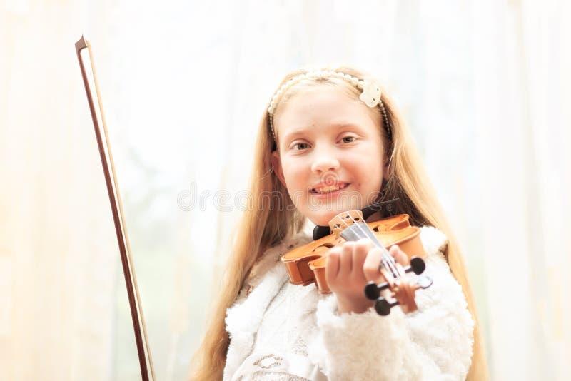 A menina joga um violino imagem de stock
