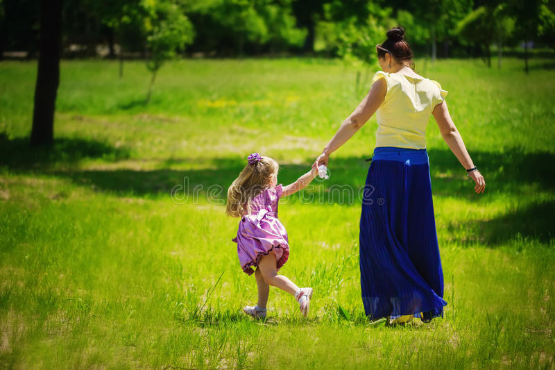 Menina junto com a mãe corrida e jogo em uma grama no foto de stock