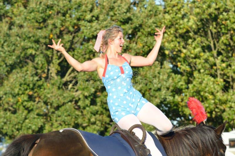 Menina justa equestre de East Anglia a cavalo que acena para aglomerar-se fotos de stock royalty free