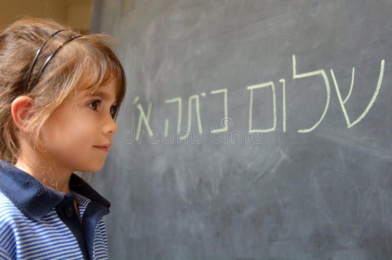 A menina lê olá! cumprimentos de primeiro grau no hebraico foto de stock