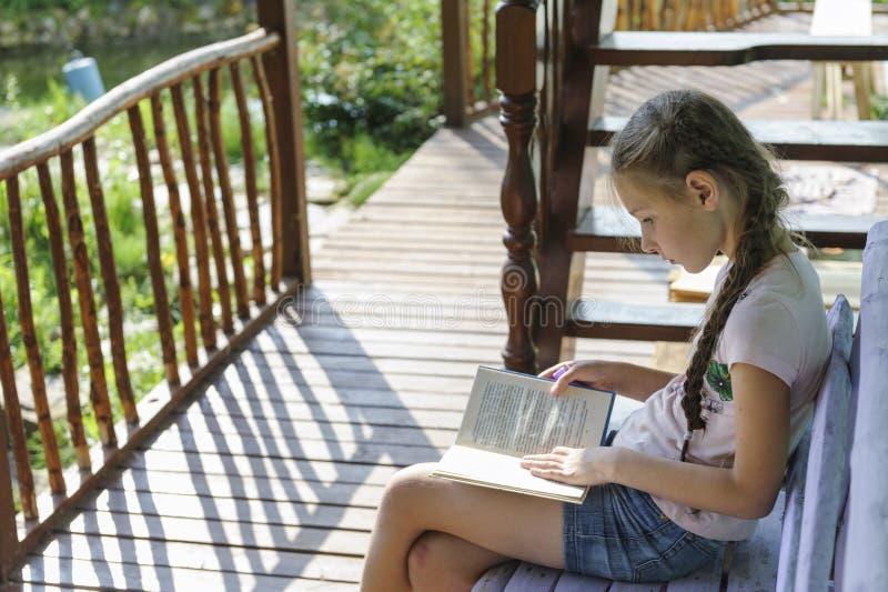 A menina lê um livro no país em um banco fotografia de stock