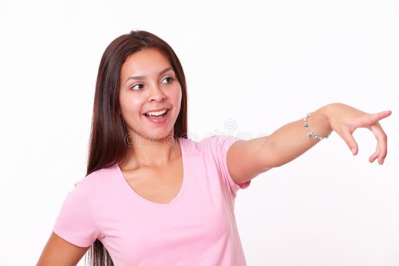 Menina latino-americano bonito que aponta a sua esquerda fotos de stock