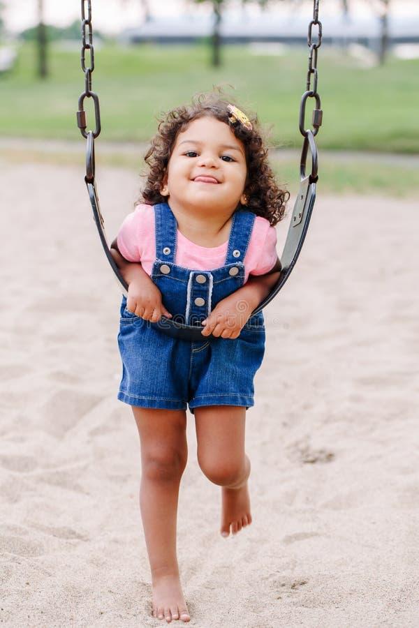 Menina latino-americano da criança do latino pequeno que balança em balanços no campo de jogos fora no dia de verão fotos de stock