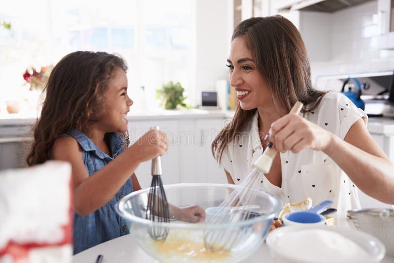 Menina latino-americano nova e seu mum que batem a mistura de bolo na cozinha e que sorriem, fim acima fotografia de stock royalty free