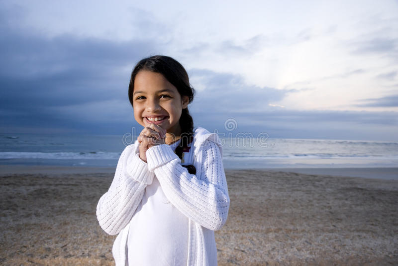 Menina latino-americano pequena bonito que sorri na praia no alvorecer foto de stock royalty free