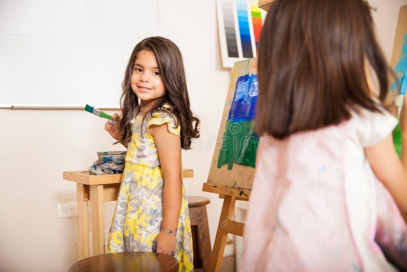 Menina latino-americano que aprecia a classe de arte imagem de stock
