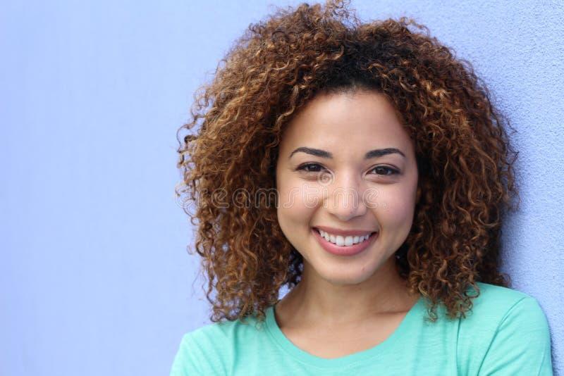 Menina latino com o retrato de sorriso do penteado afro louro em um fundo azul com espaço da cópia imagens de stock
