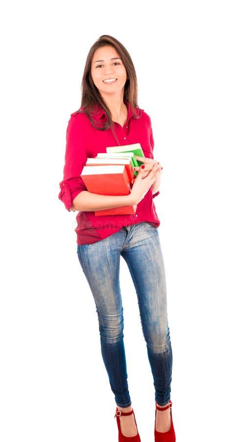 Menina latino nova que guarda a pilha dos livros fotografia de stock royalty free