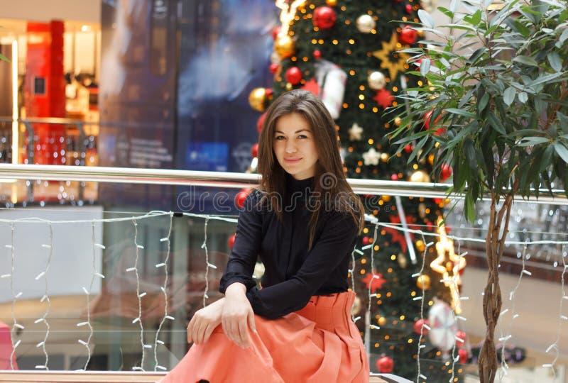 A menina levanta contra o fundo de uma árvore de Natal imagem de stock