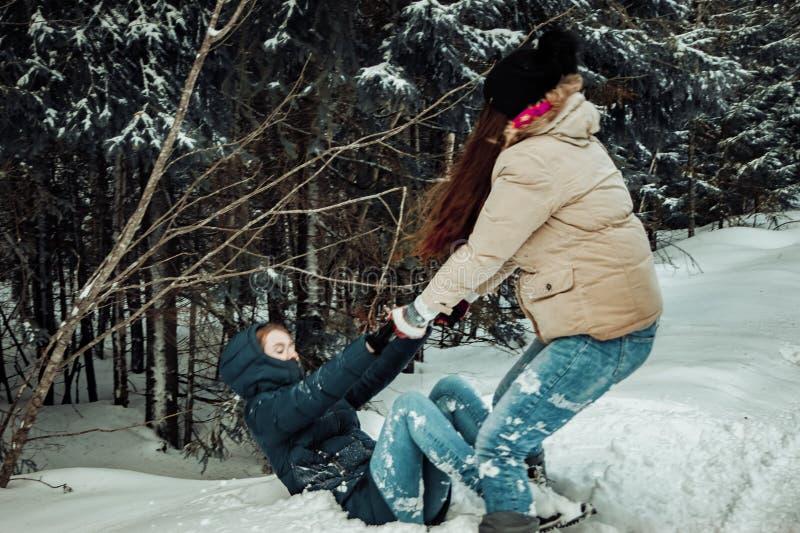 A menina levanta seu amigo fora da neve fotografia de stock