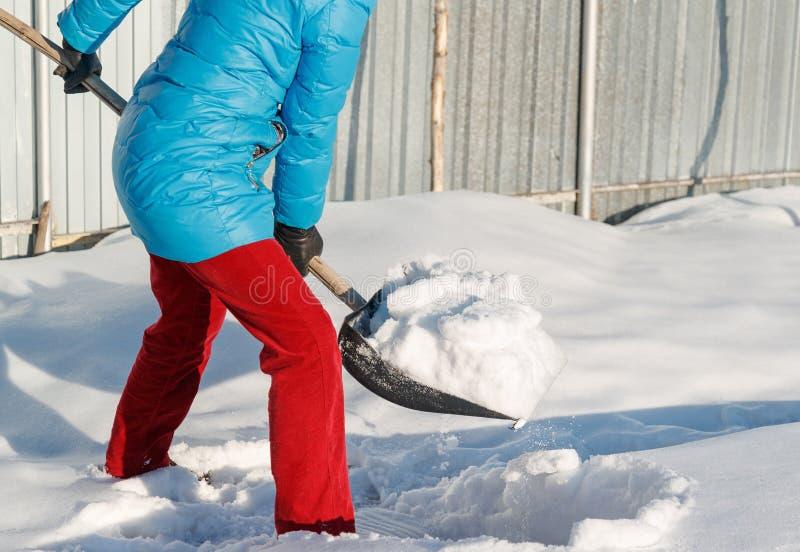 A menina limpa a pá da neve no local perto de sua casa sunlight fotos de stock