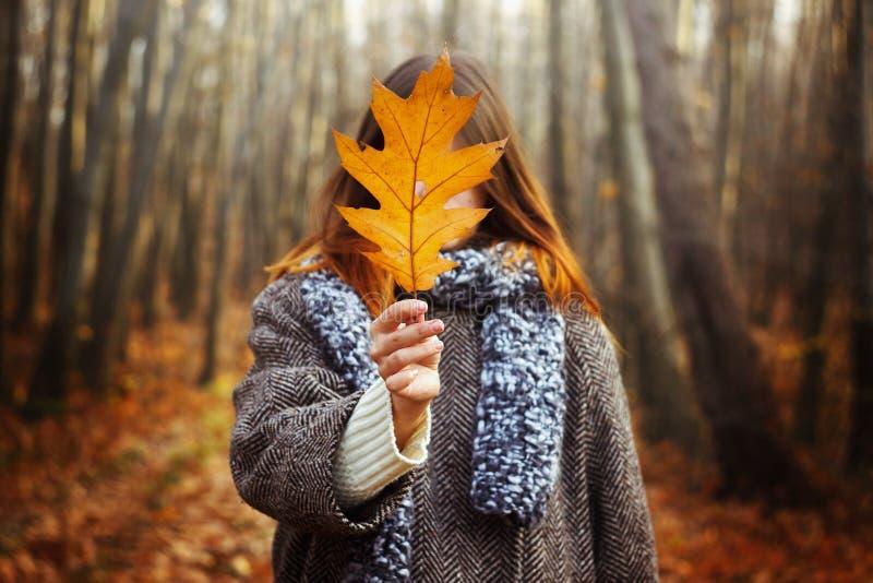 Menina lindo feliz à moda bonita que guarda a folha amarela no th imagem de stock