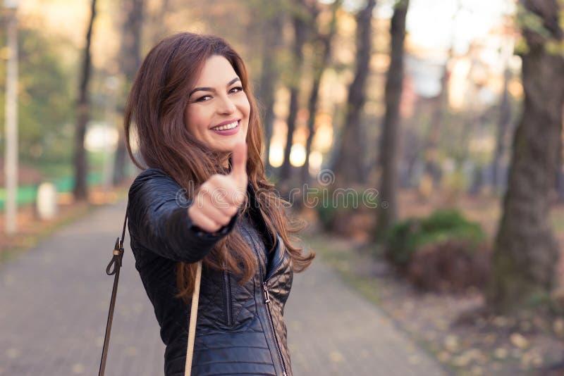 Menina lindo no polegar de aumentação do parque do outono acima imagens de stock