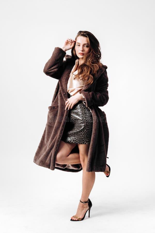 A menina lindo vestida em uma camisa, em uma saia do leopardo e em um casaco de pele nos saltos altos levanta no fundo branco no  imagens de stock