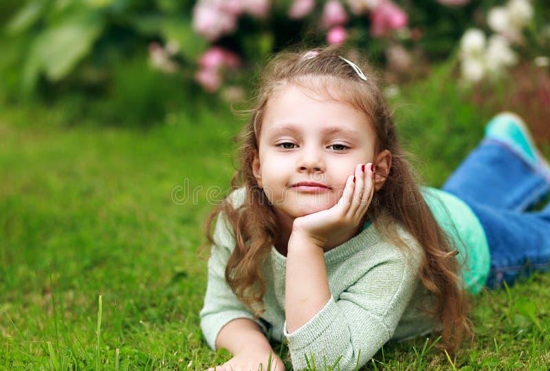 Menina longa bonita da criança do cabelo encaracolado que encontra-se na grama verde no fashi imagem de stock royalty free