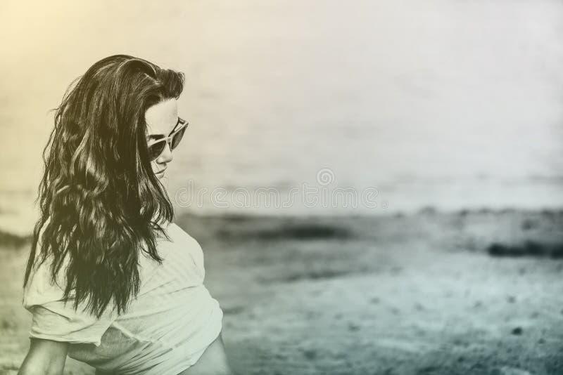Menina longa do cabelo que relaxa na praia imagens de stock royalty free
