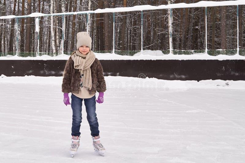 Menina longhair nova que veste na roupa ocasional do inverno na pista de gelo fotografia de stock