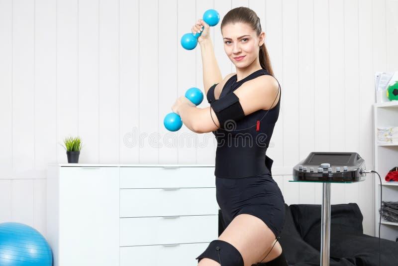 A menina loura é contratada no terno muscular bonde da estimulação com foto de stock