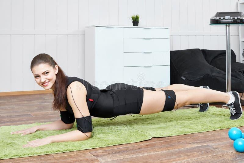 A menina loura é contratada no terno muscular bonde da estimulação com imagem de stock