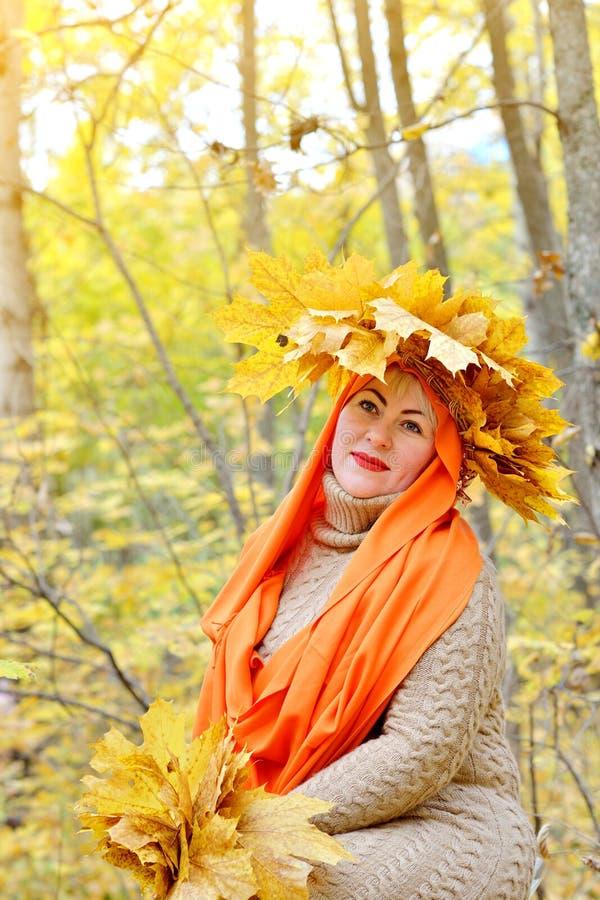 A menina loura é um grande tamanho em uma grinalda das folhas de outono que sentam-se e que sorriem na floresta em um fundo amare imagem de stock royalty free