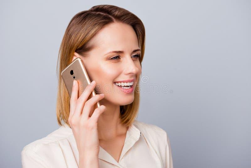 A menina loura alegre com sorriso de irradiação está falando em seu telefone imagens de stock