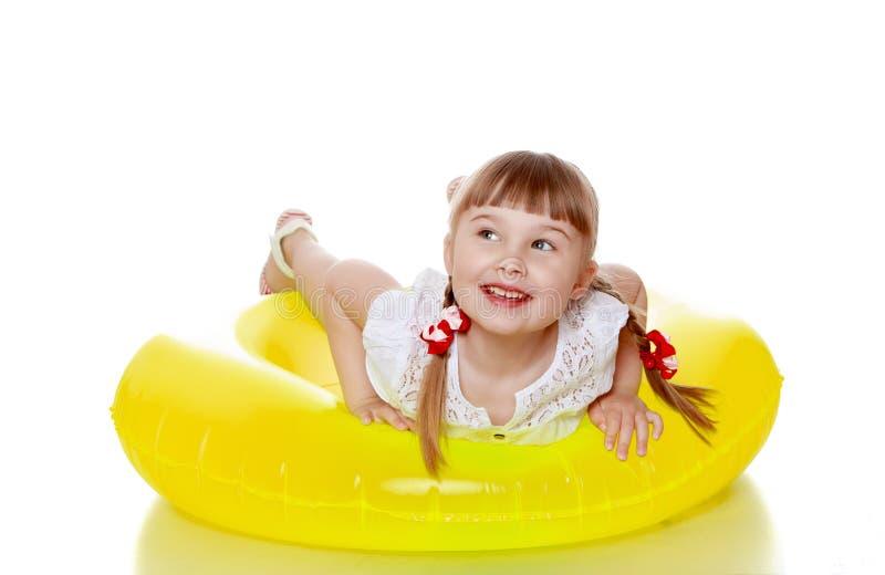 A menina loura alegre feliz com tranças está na fotografia de stock