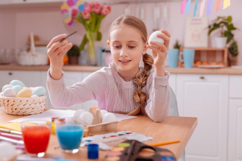 Menina loura alegre que toma o ovo limpo do suporte fotografia de stock