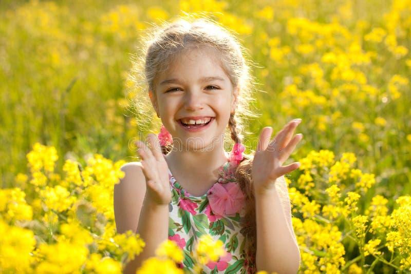 A menina loura aplaude suas mãos fotos de stock royalty free
