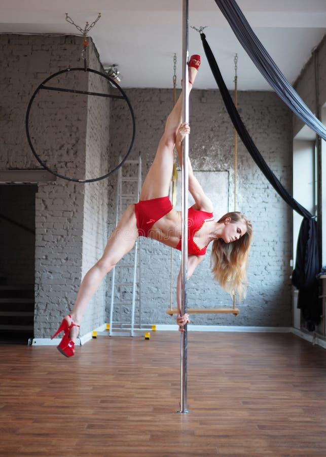 menina loura apta que faz um conluio no pilão Exercício da dança de Polo Parte superior vermelha e cuecas sobre e saltos altos ve fotos de stock