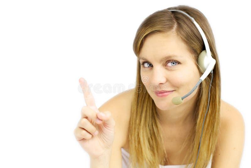 A menina loura atrativa com auriculares mostra seu texto fotos de stock